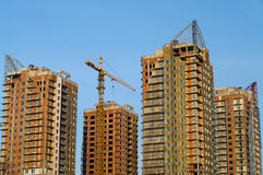 Four high-rise buildings under construction. On a blue sky background Stock Images
