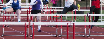 Four high school girls racing the hurdles. Four girls racing the hurdles during a high school competition outdoors in the early spring royalty free stock image