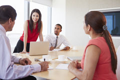Four Hispanic Businesspeople Having Meeting In Boardroom Stock Image