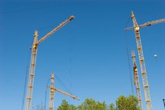Four hoisting cranes Stock Photos