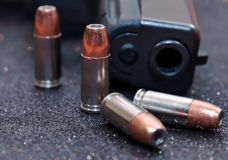 Four hollow point bullets with a black pistol. Four hollow point 9mm bullets with a black pistol Royalty Free Stock Photography
