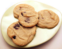 Four homemade cookies. Homemade chocolate chip cookies on small green plate Royalty Free Stock Images