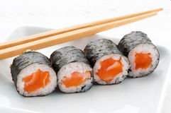 Four Hosomaki salmon sushi. Wound in rice and sea weed served as an appetizer with chopsticks Stock Image