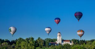 Many hot air balloons hover over the Train Depot in Boise Idaho. Four hot air balloons float over the Boise train depot Royalty Free Stock Images