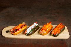 Four hot dogs on wooden chopping board. royalty free stock photo