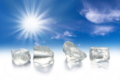 Four ice cubes, sun and blue sky Stock Image