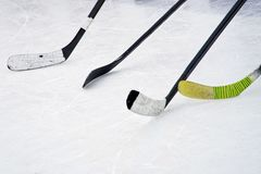 Four ice hockey sticks on the ice. Preparation for training in an open area. Winter sports royalty free stock images