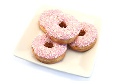 Four Iced Doughnuts with Sprinkles. Iced donuts and sprinkles on a cream china plate Royalty Free Stock Photography
