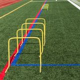 24 inch yellow banana step hurdles on turf field. Four 24 inch yellow banana step hurdles are set up on a turf fied for athletes to jump over followed by some 6 royalty free stock images