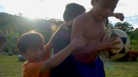 Indigenous boys are fighting to get a ball while playing outside. Four indigenous boys are fighting to get a ball while playing outside in their native village stock video footage