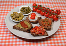Italian bruschetta plate. Four italian delicious bruschetta on a round plate Royalty Free Stock Images
