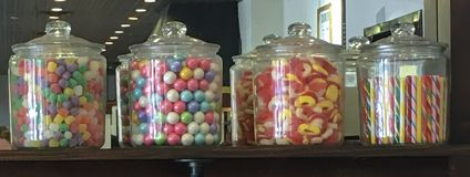 Four jars filled with various candies stock images