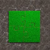 Four jigsaw puzzles with green grass stock image