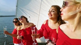 Four joyful women relaxing with wine at sailboat party. Joyful women in red clothes relaxing at sailboat party in sunny weather. Four attractive girls dancing stock video