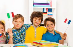 Four kids with banners on cheeks waving flags Royalty Free Stock Photo