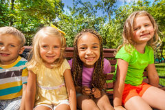 Four kids on the bench in park Royalty Free Stock Photos