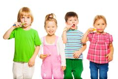 Four kids brushing teeth stock photo