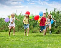 Four kids with colorful balloons Royalty Free Stock Photo