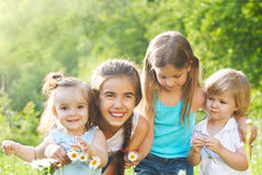 Four kids in the daisy spring field Royalty Free Stock Photography