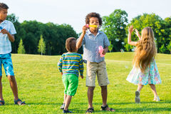 Four kids on glade with soap bubble. Royalty Free Stock Images
