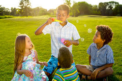 Four kids on glade with soap bubble. Four children are playing on the evening glade. They are making soap bubble and catching its stock photography