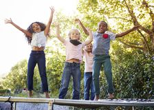 Four kids having fun together on a trampoline in the garden stock images