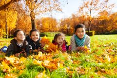 Four kids lay in autumn leaves Royalty Free Stock Image