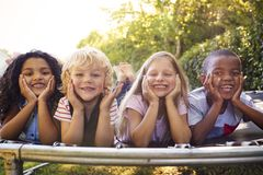 Four kids lying down together on a trampoline in the garden royalty free stock images