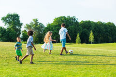 Four kids are playing on evening glade. Stock Image