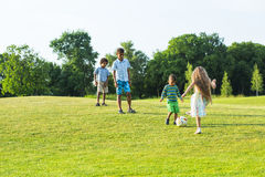 Four kids are playing on evening glade. Stock Photos