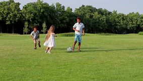 Four kids are playing on evening glade. stock video footage