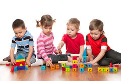 Four kids are playing on the floor. With blocks stock photography