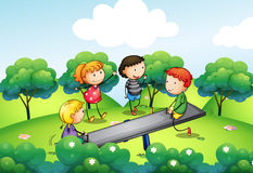 Four kids playing with the seesaw at the hill Stock Image