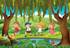 Four kids running in the park Stock Photo