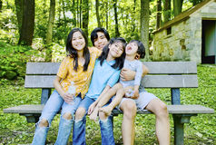 Four kids sitting on bench Stock Photos