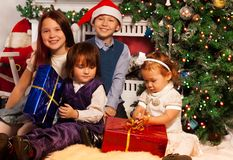 Four kids sitting side by side to fireplace Royalty Free Stock Photo