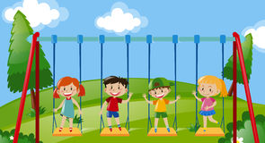 Four kids on swings in the park Stock Photography
