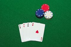 Four of a Kind. Poker hand, four aces with red, white and blue poker chips, against a green felt background Stock Image