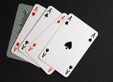 Four of kind poker combination. Closeup of five playing cards: four ace and one back stock images