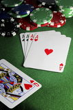 Four of a Kind Poker Hand with Chips. Four aces and queen of hearts poker hand with casino chips on green felt stock photography