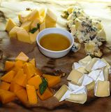 Four kinds of cheese with honey and bread stock photo