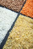 Four kinds of organic cereals: rice, bulgur, buckwheat and lentils on a black background stock photos