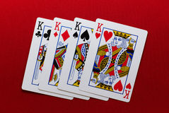 Four kings. Playing cards four of kings over red felt Royalty Free Stock Photos