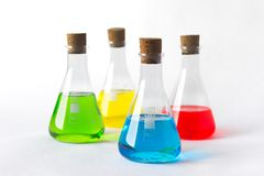 Four laboratory flasks with cork plugs and colorful liquids stock photography