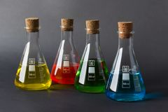 Four laboratory flasks with cork plugs and liquids stock photography