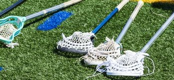 Four lacrosse sticks laying on the turf. Four high school boys lacrosse sticks are laying down on a green turf field stock photography