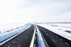 Four-lane highway in winter. Four-lane highway leads across the country in winter Royalty Free Stock Photo
