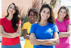 Four laughing girlfriends in colorful shirts in the city Royalty Free Stock Images