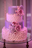 Four-layer wedding cake. Photo closeup of traditional elegant delicious sweet four-layer wedding cake decorated with butter-cream roses on glass stand on blurred Royalty Free Stock Image