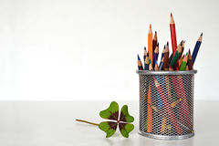 Four-leaf clover and colorful pencils Stock Photos